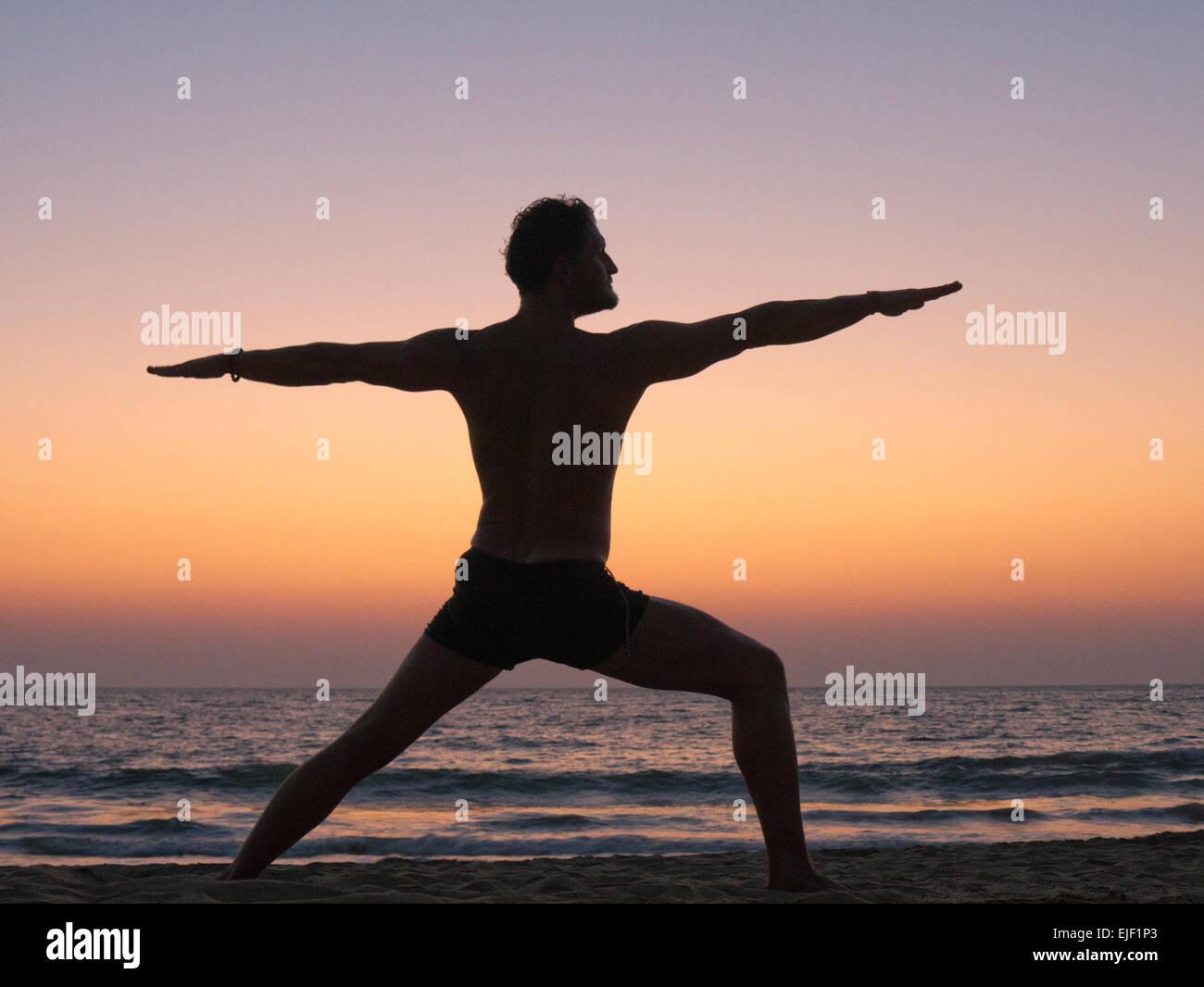 Ein Mann üben Yoga-Krieger-Pose am Strand Stockbild