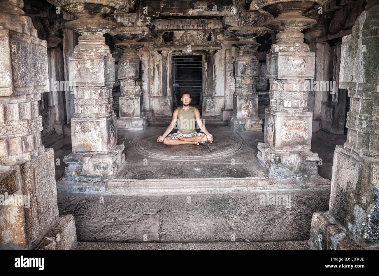 Mann tut Meditation in antiken Tempel mit carving Spalten in Hampi, Karnataka, Indien Stockbild