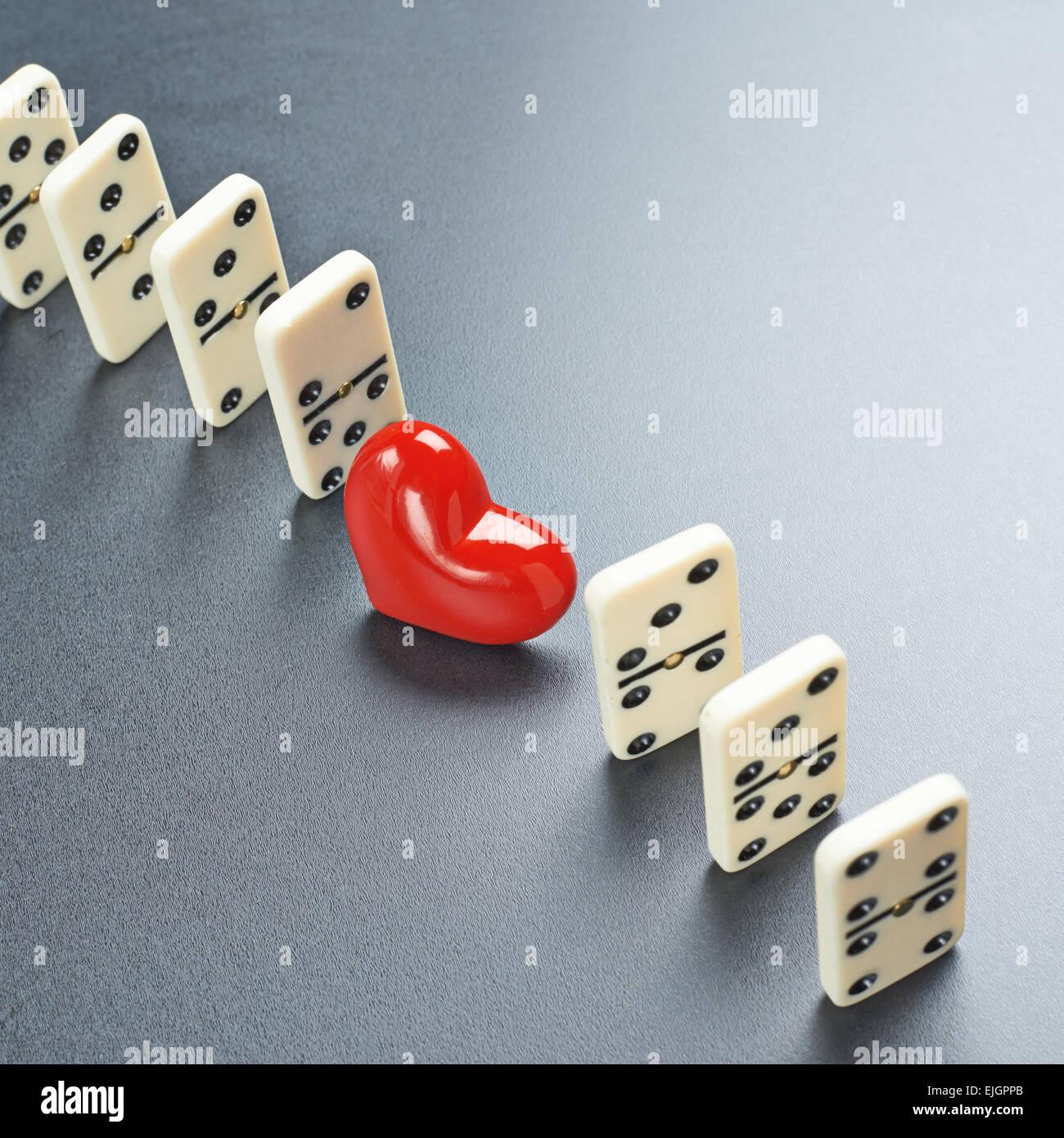 Rotes Herz zwischen den Domino-Stücken Stockfoto