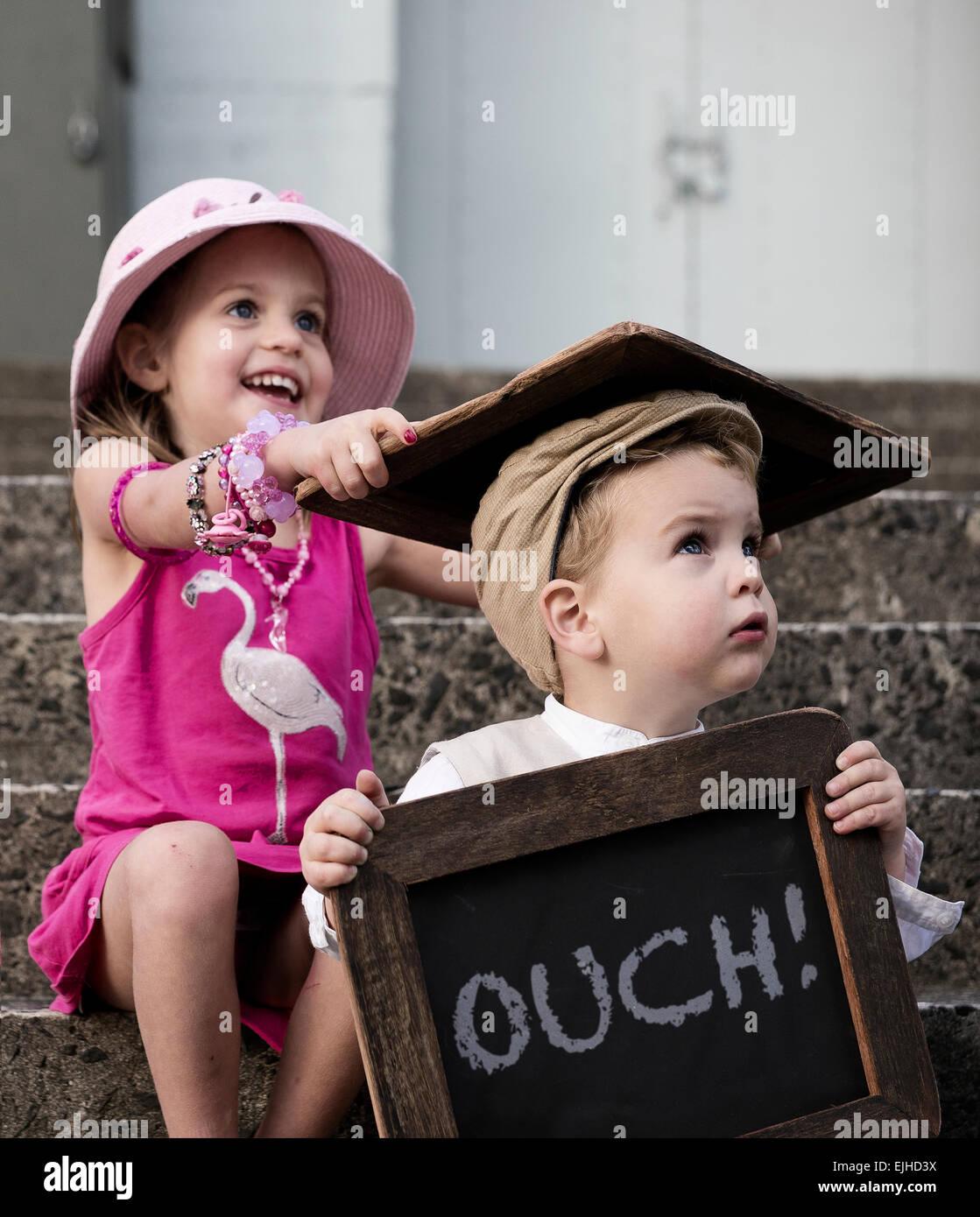 Freche Schwester trifft ihr Bruder über den Kopf mit Tafel Stockbild