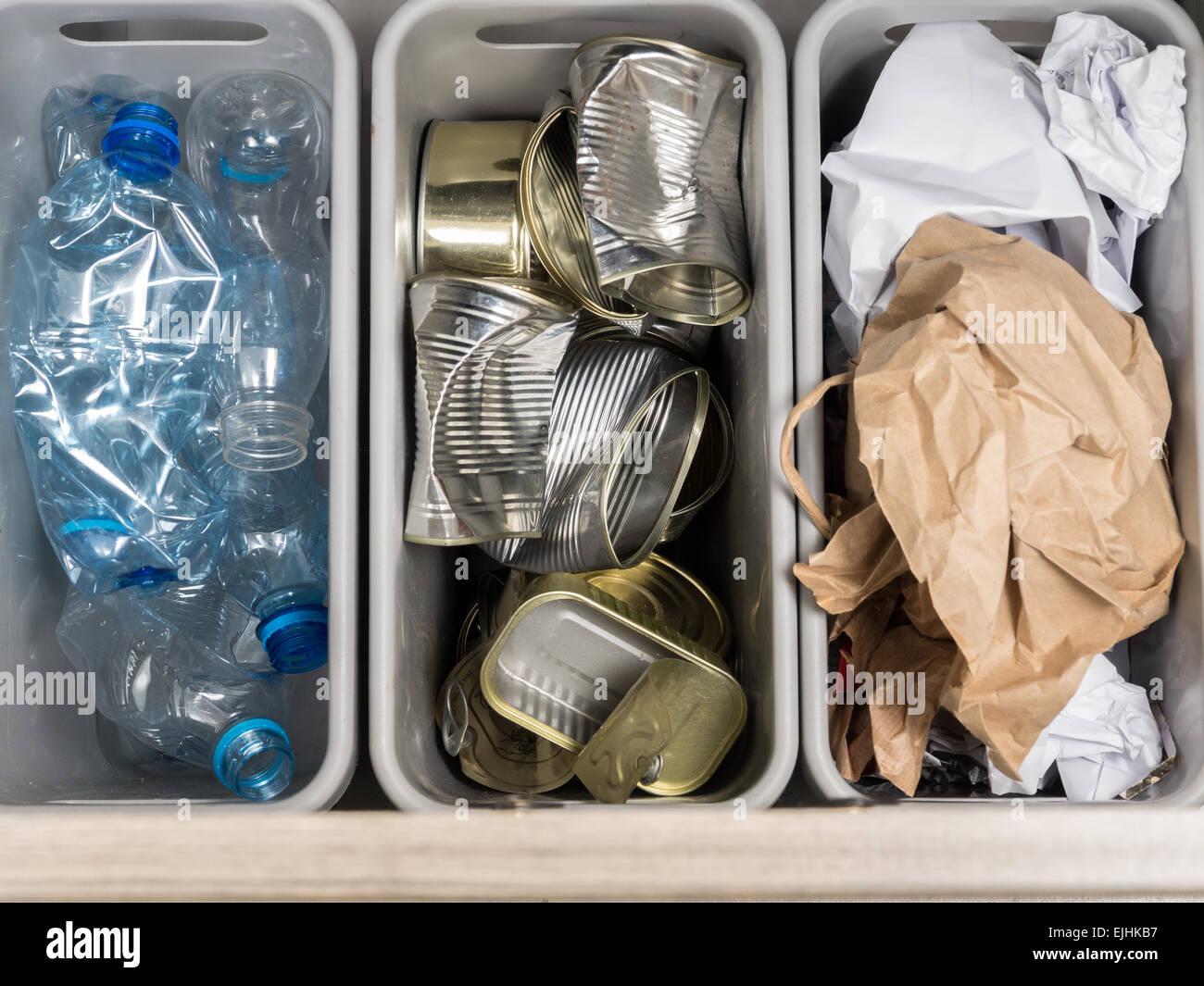 Drei Kunststoff Mülltonnen mit getrennten Hausmüll - PET-Flaschen, Papier und Metall Dosen von oben geschossen. Stockbild