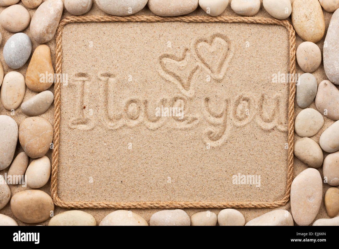 Schöner Rahmen aus Seil und Muscheln im Sand mit Text ich liebe dich ...