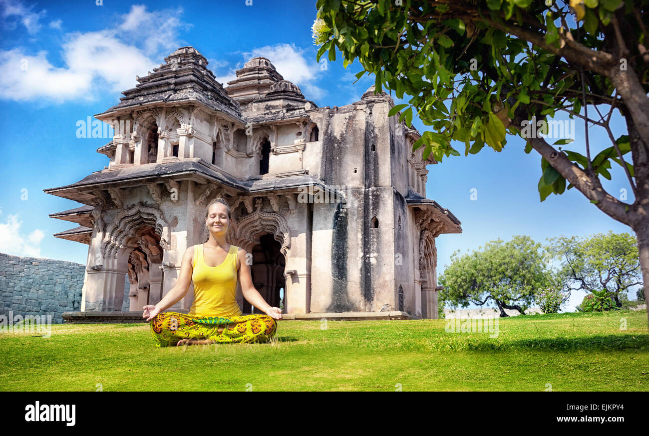 Frau beim Yoga in der Nähe von Lotus Mahal im königlichen Center am blauen Himmel in Hampi, Karnataka, Stockbild