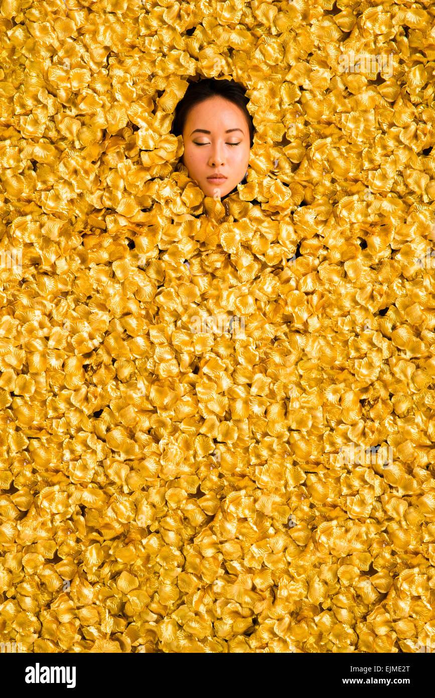 Luxus: Ein junger, die ethnische chinesische Frau Mädchen liegen in einem Bad, umgeben von Tausenden von golden Stockbild
