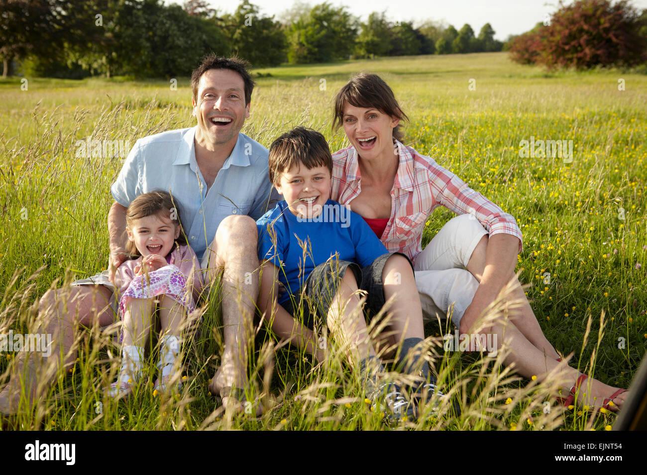 Eine Familie, zwei Eltern und zwei Kinder im Freien an einem Sommerabend. Stockbild