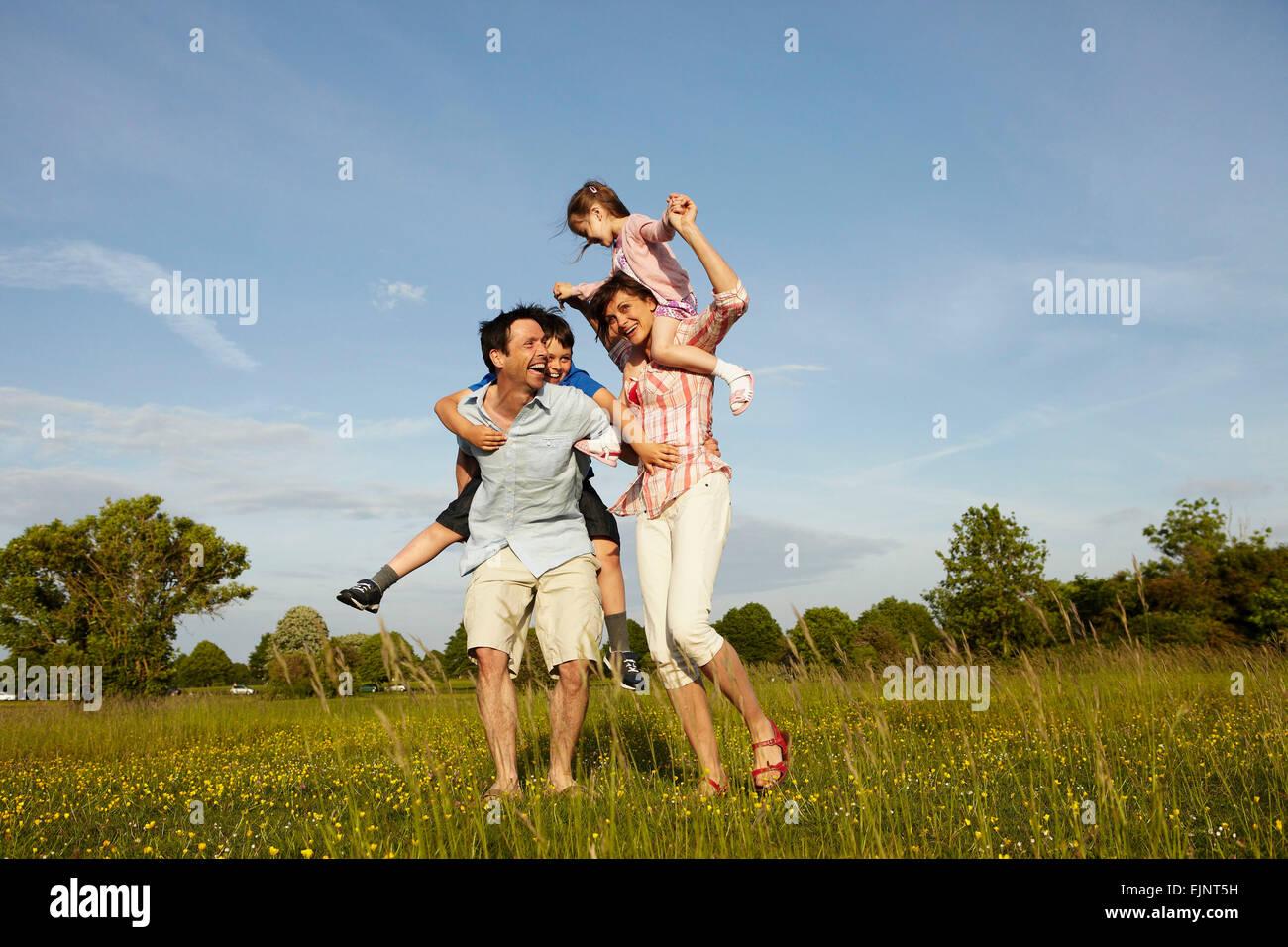 Eine Familie, zwei Eltern im Freien im Sommer geben piggybacks für zwei Kinder. Stockbild