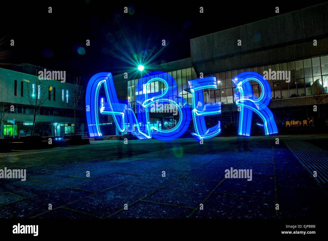 """Lightbombing / Licht-Malerei - das Wort """"ABER"""" in Licht außerhalb Aberystwyth Arts Centre in der Nacht Wales UK gemalt Stockfoto"""