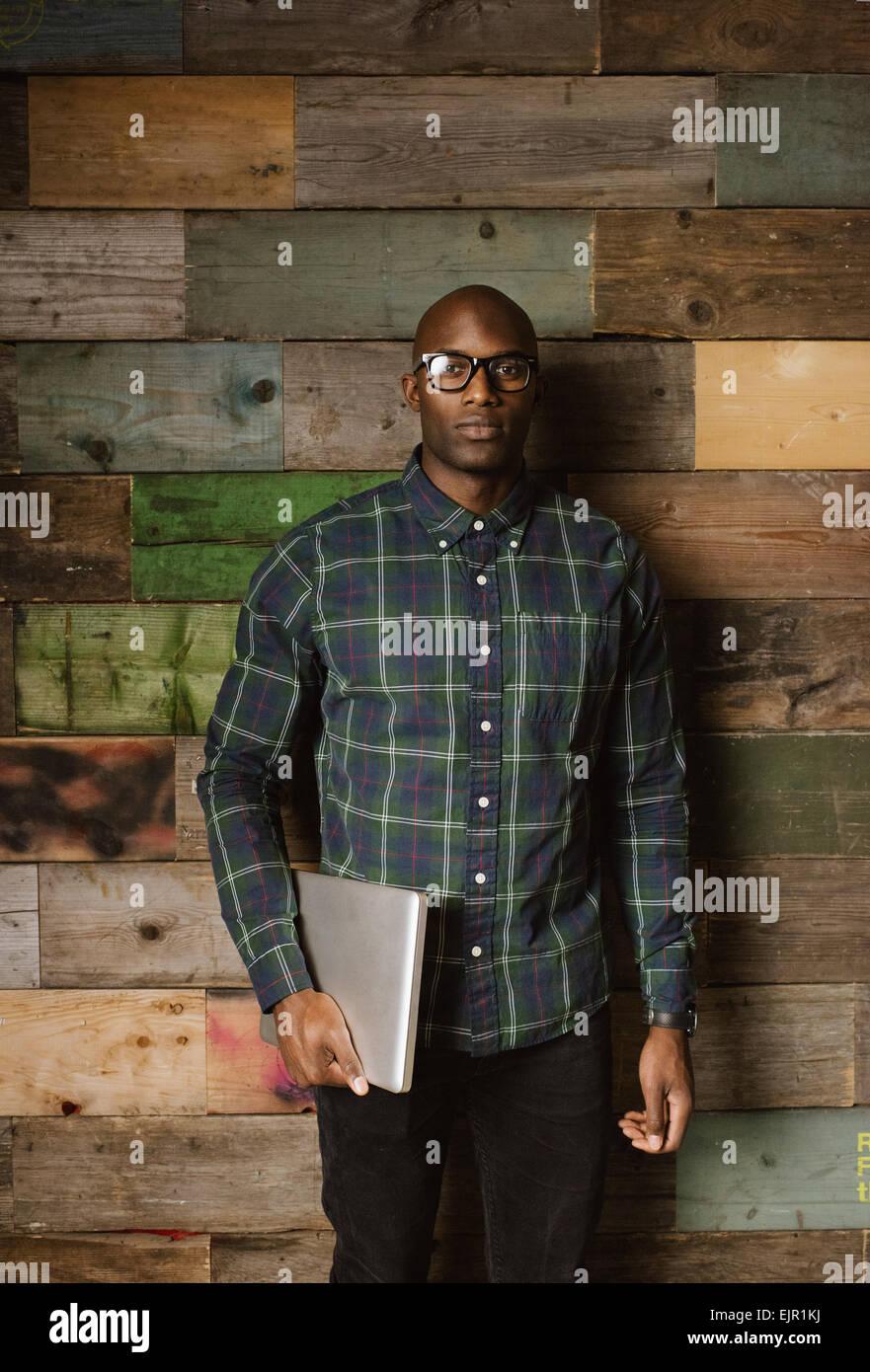 Porträt von schweren jungen afrikanischen Mann mit einem Laptop, Blick in die Kamera stehend gegen eine Holzwand Stockbild
