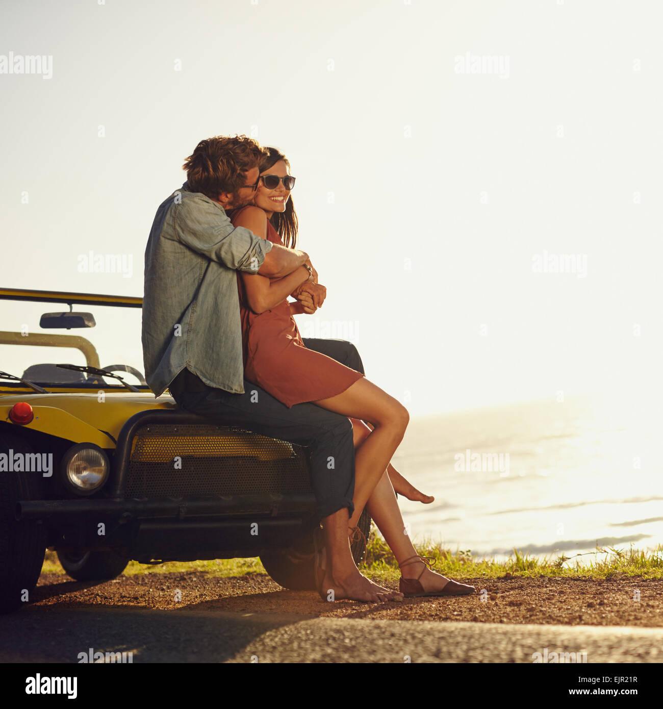Junges Paar in Liebe umarmen und küssen. Junger Mann und Frau sitzen auf der Motorhaube. Romantische junges Paar Stockfoto