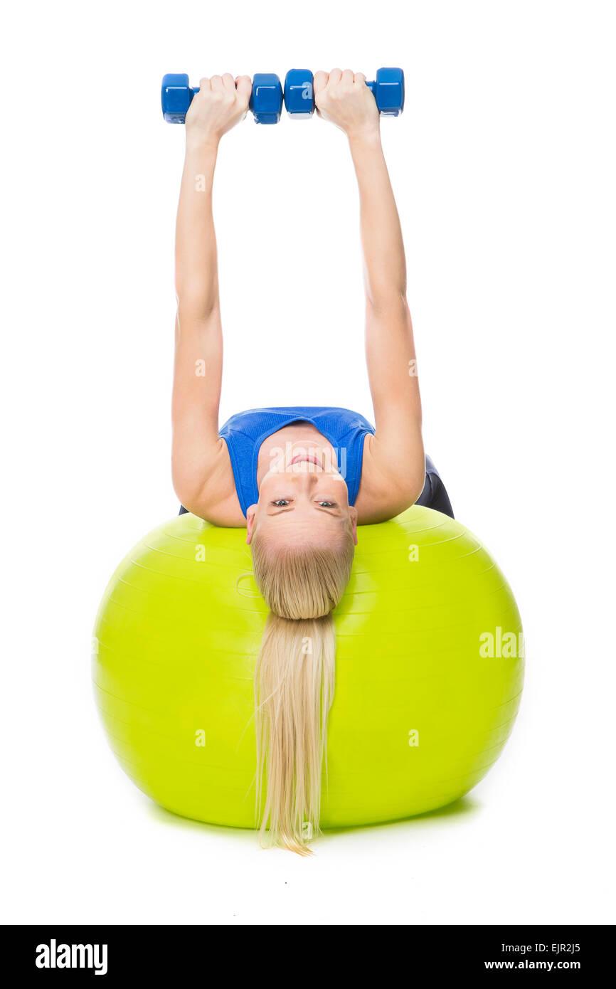 blonde Frau trägt Fitness Kleidung Training mit Gewichten auf eine gelbe Kugel Stockbild