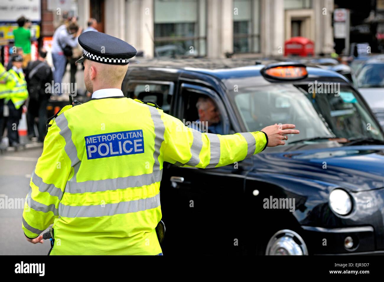 London, England, Vereinigtes Königreich. Schwarzen Taxifahrer bestreiten, 2014. Polizist der Verkehrslenkung Stockbild