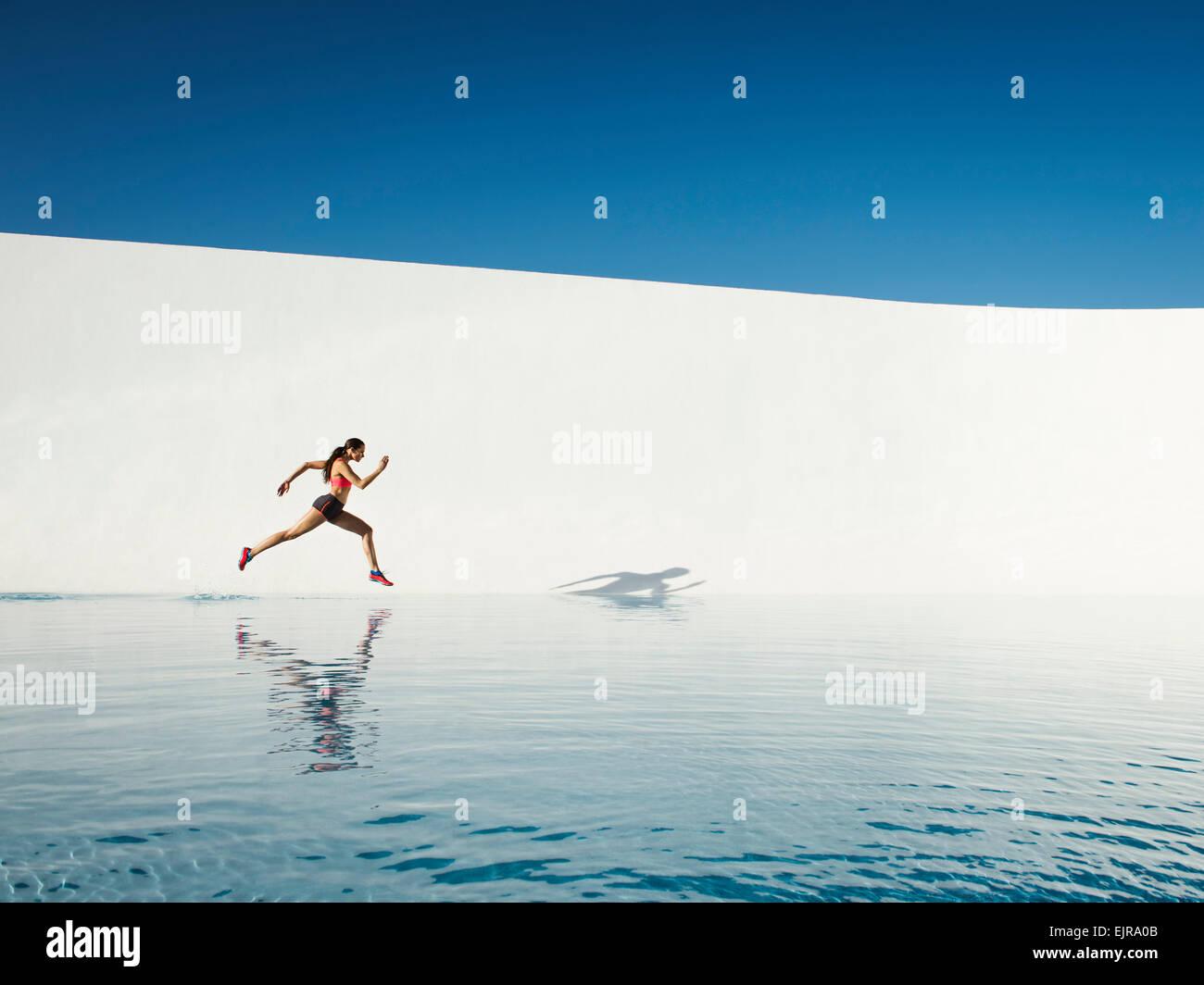 Kaukasische Frau läuft auf Wasseroberfläche Stockfoto