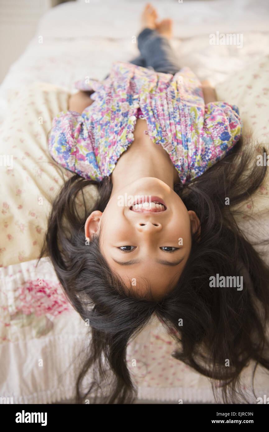 Lächelnde vietnamesisches Mädchen auf Bett Stockfoto