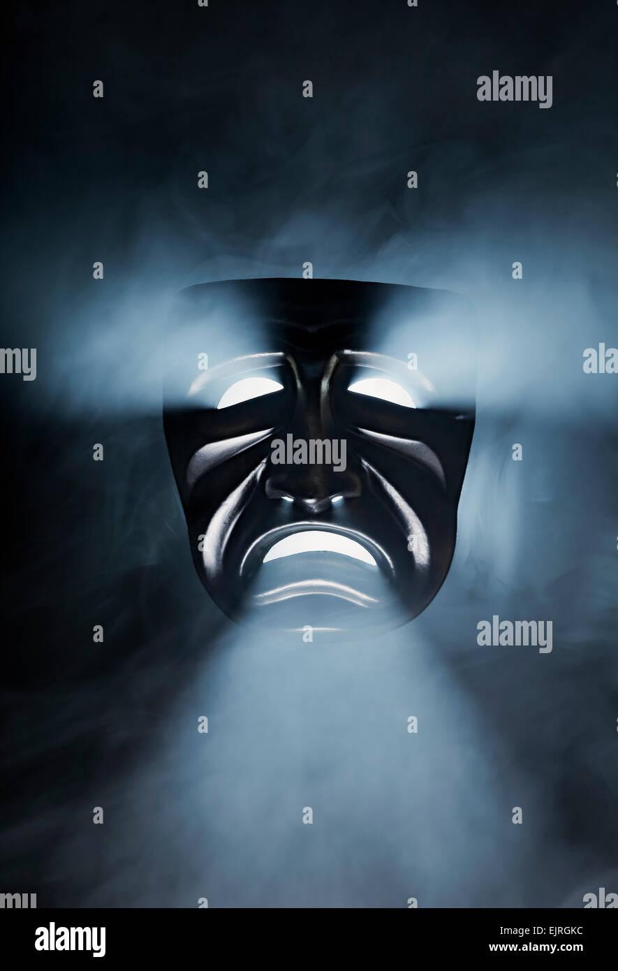Eine schwarze traurige Maske in rauchigen Gegenlicht. Stockbild