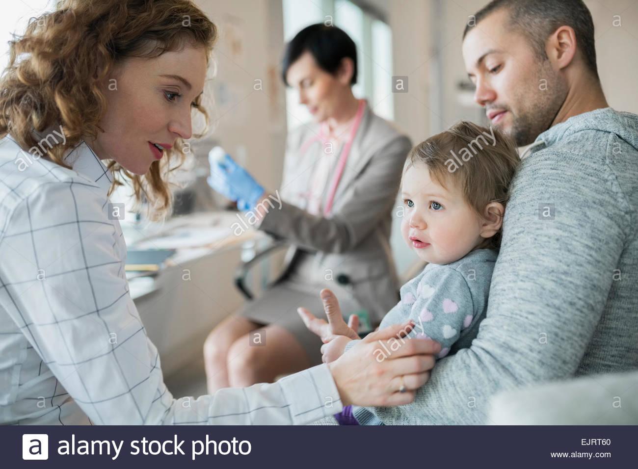 Eltern halten Babymädchen Kinderarzt Impfung wird vorbereitet Stockbild