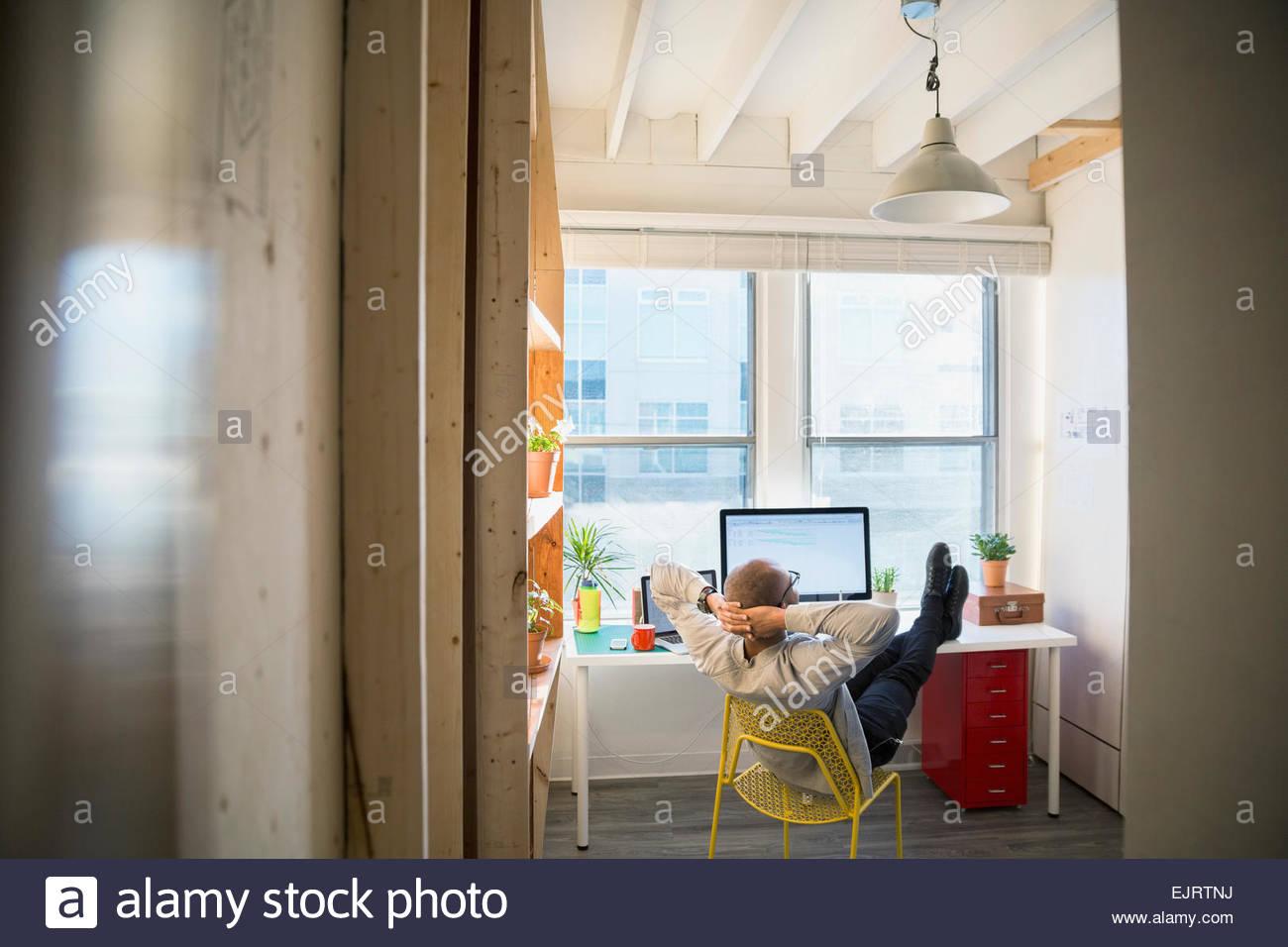 Designer mit den Füßen oben auf Schreibtisch Stockbild