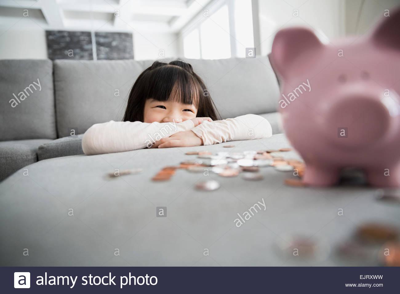 Lächelndes Mädchen mit Sparschwein und Münzen Stockfoto