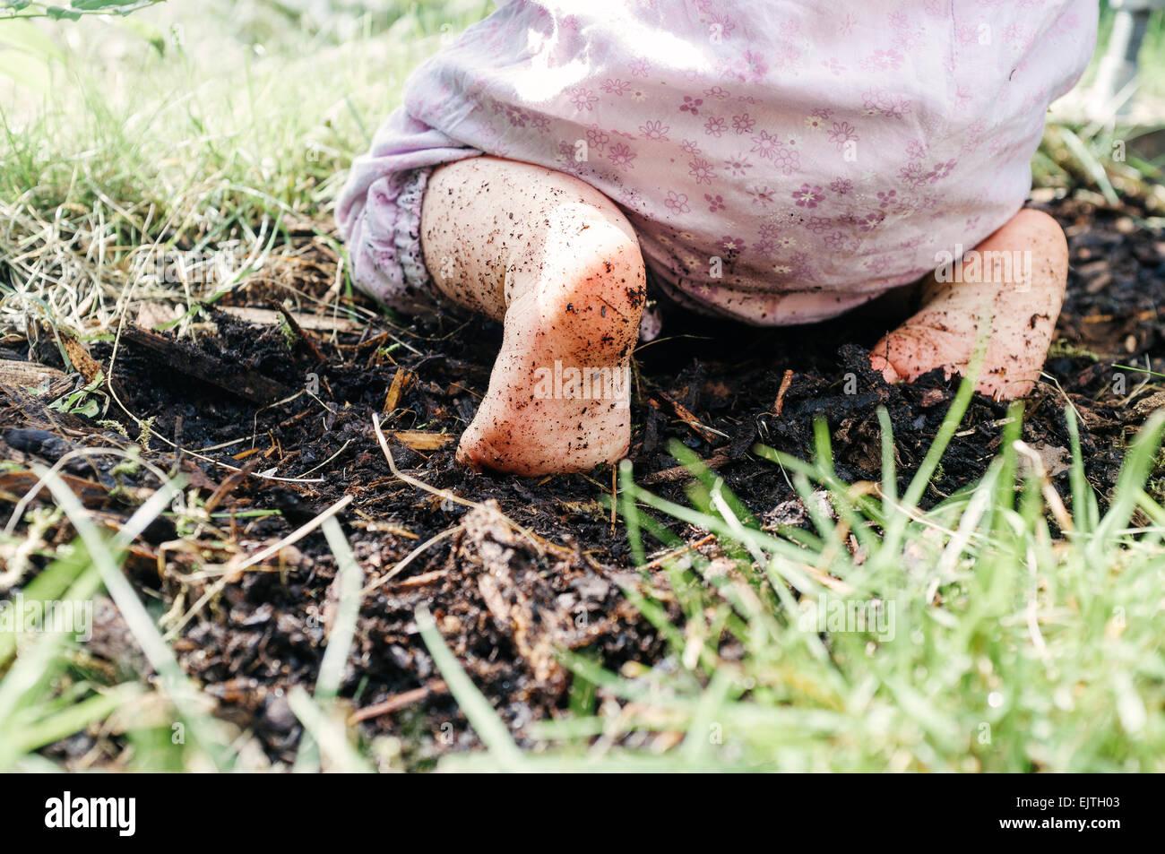 Geringen Teil Baby mit schmutzigen Füßen kniend auf Schmutz Stockbild
