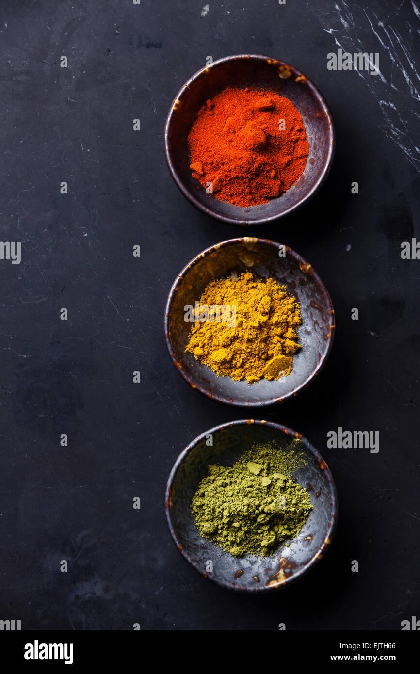 Gewürze-Curry, Paprika, Matcha-Tee auf dunklem Marmor Stockbild