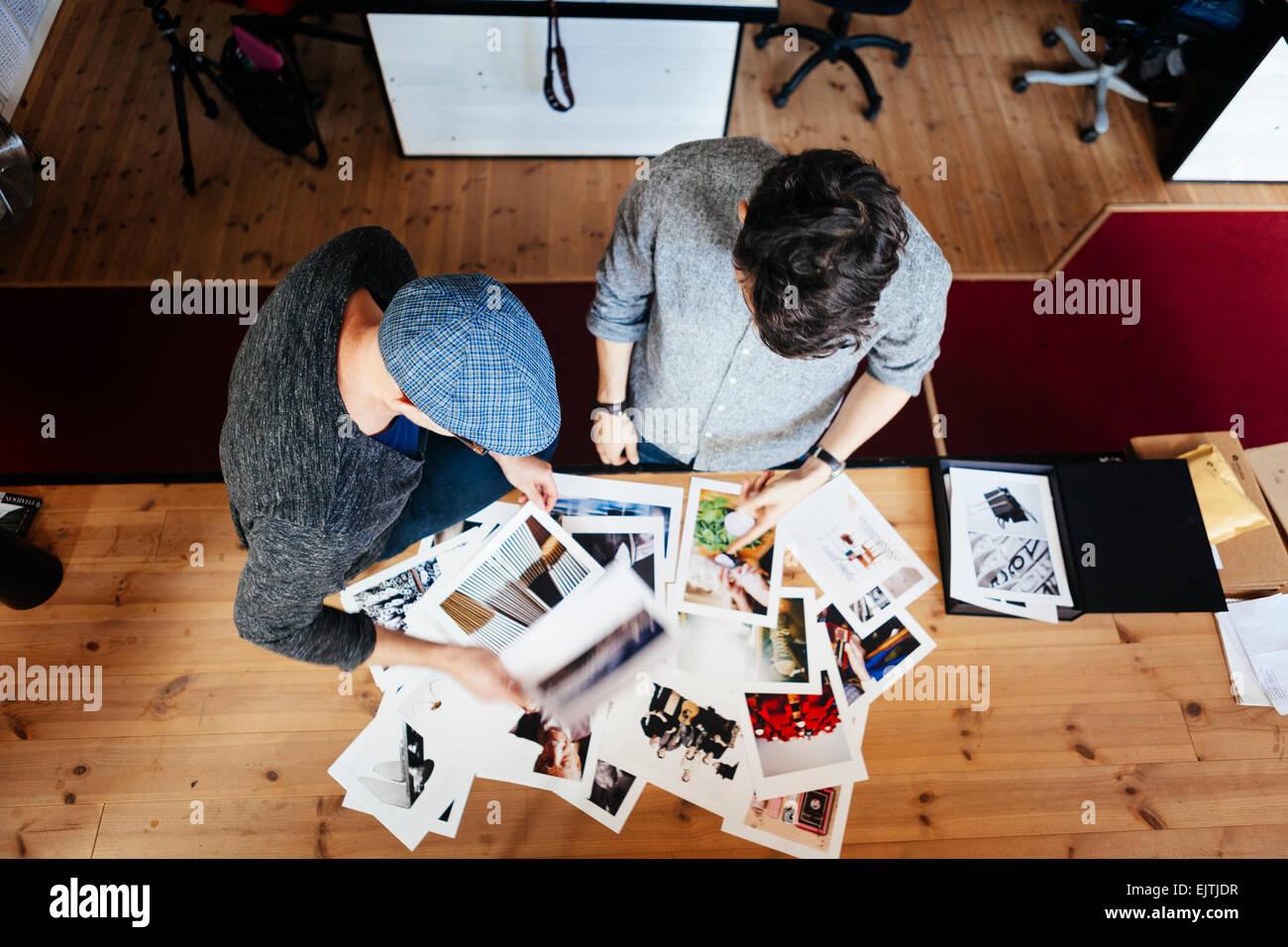 Erhöhte Ansicht von Geschäftsleuten, die Analyse von Fotografien am Schreibtisch im Büro Stockbild