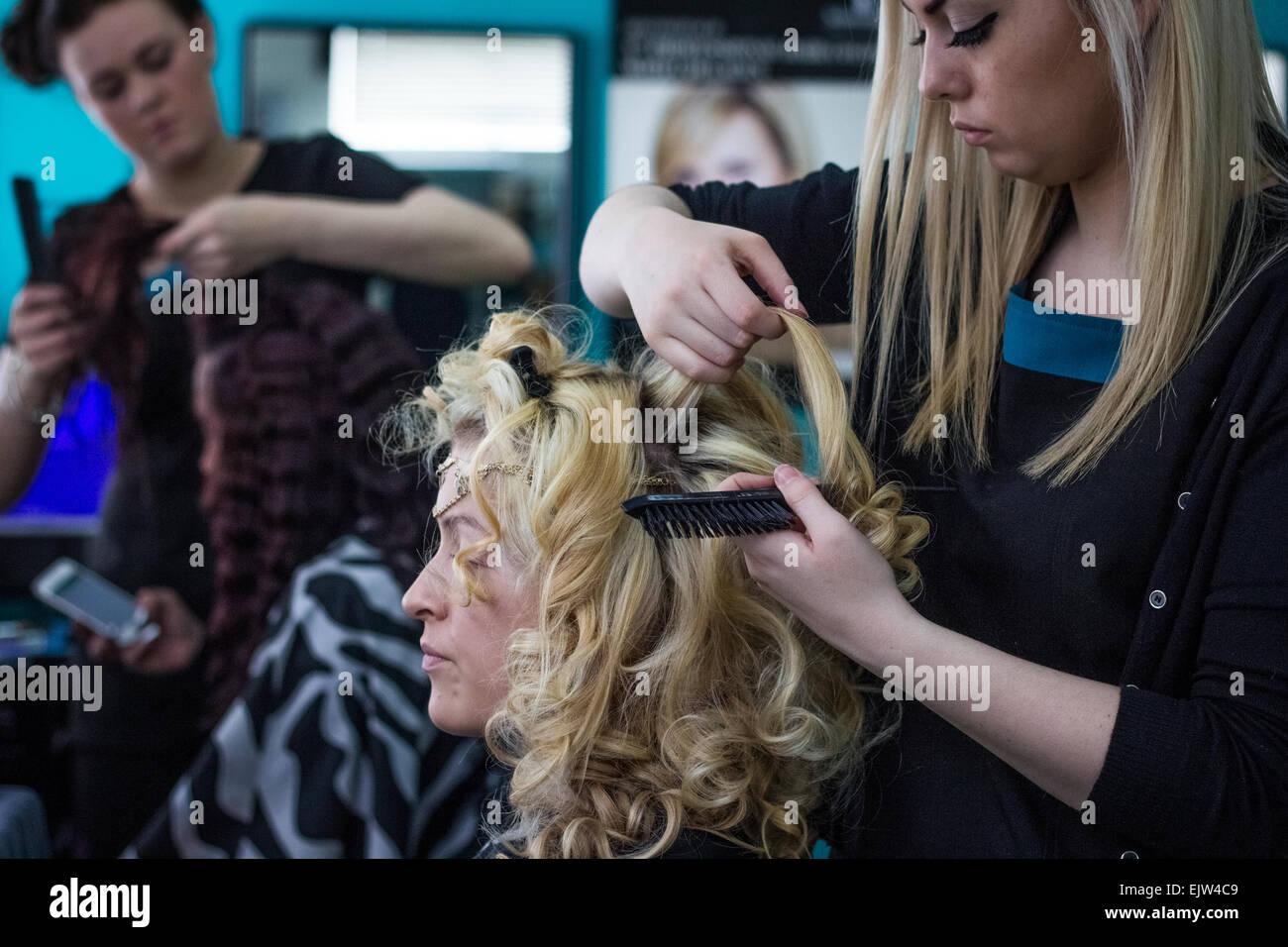 Friseure arbeiten in einem Salon in Uniform auf weibliche Modelle mit lockigem Haar, blond, eine Brünette. Stockbild