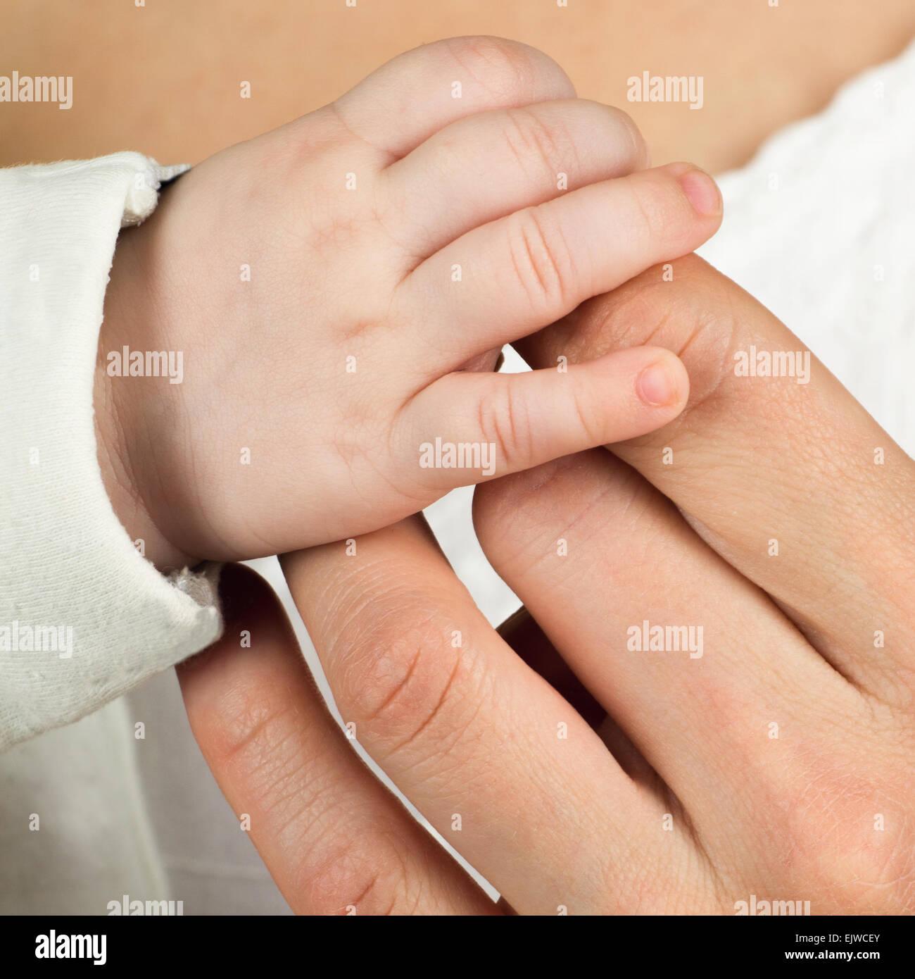 Kinderhand mit Mutter finger Stockbild