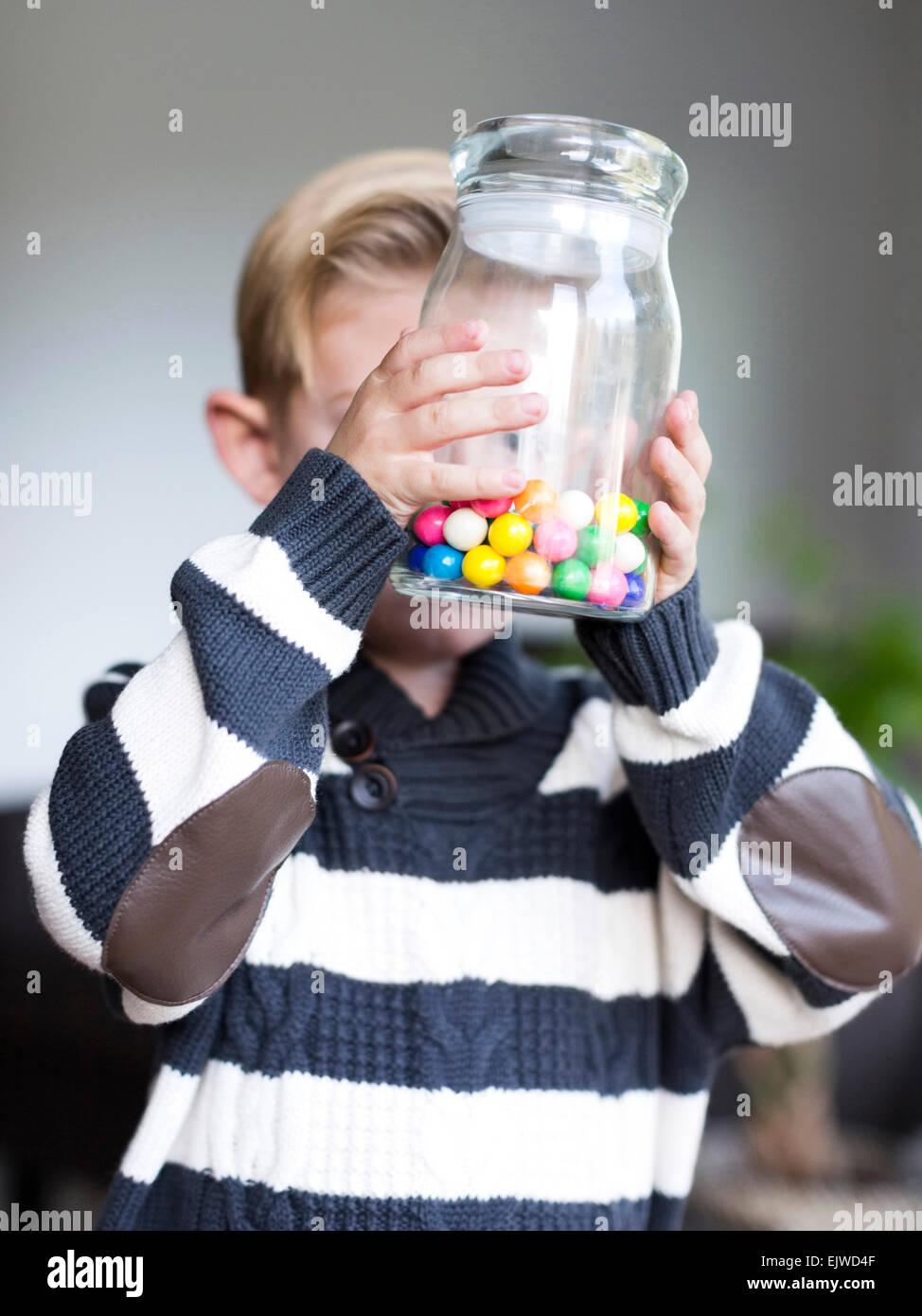 Junge (6-7) halten Glas Glas mit Süßigkeiten Stockbild