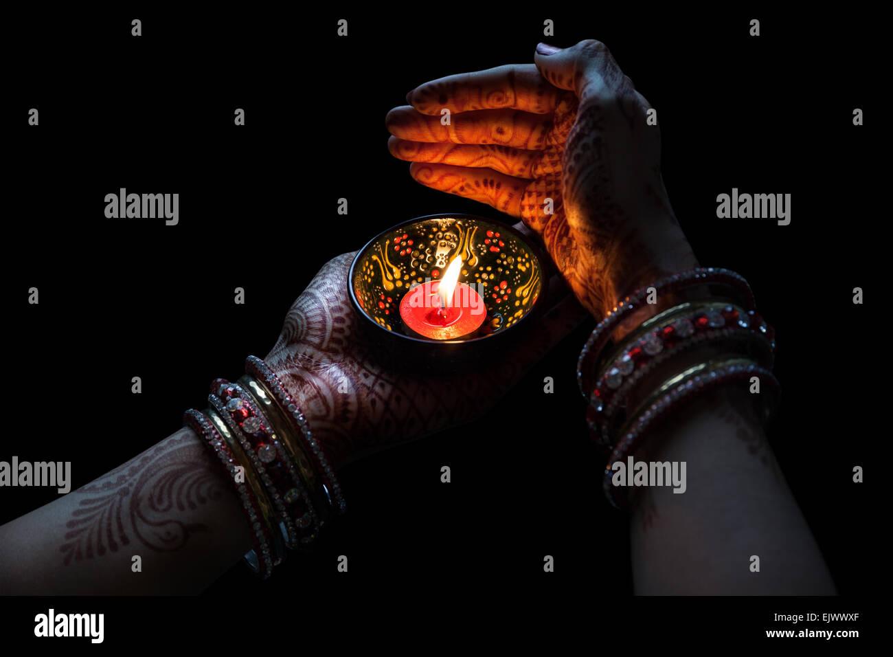 Frau Hände mit Henna mit Kerze auf Beschneidungspfad auf schwarzem Hintergrund isoliert Stockbild