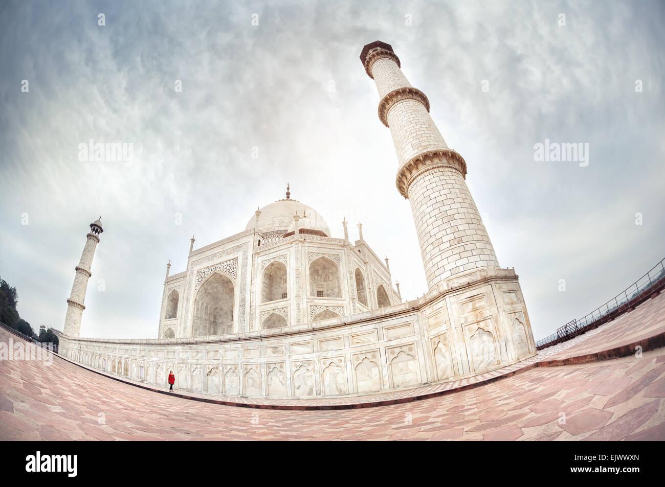 Frau in rot, die zu Fuß in der Nähe von Taj Mahal in dramatischen Himmel in Agra, Uttar Pradesh, Indien Stockbild