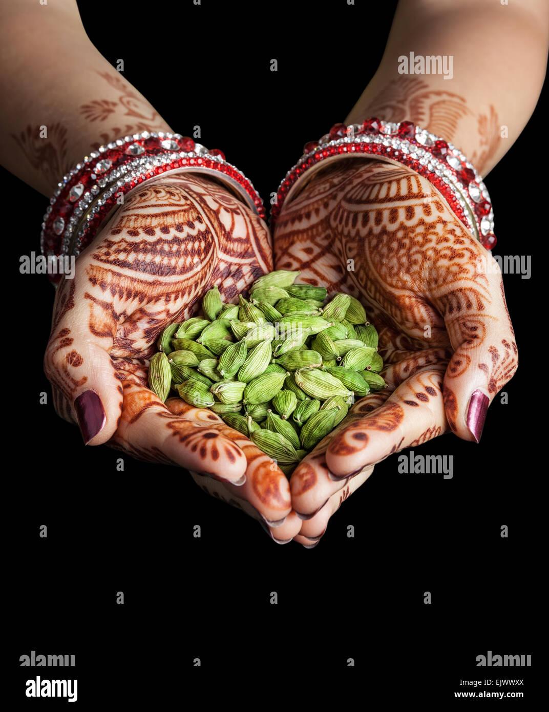 Frau die Hände mit Henna hält grüner Kardamom-Gewürze isoliert auf schwarzem Hintergrund mit Stockbild