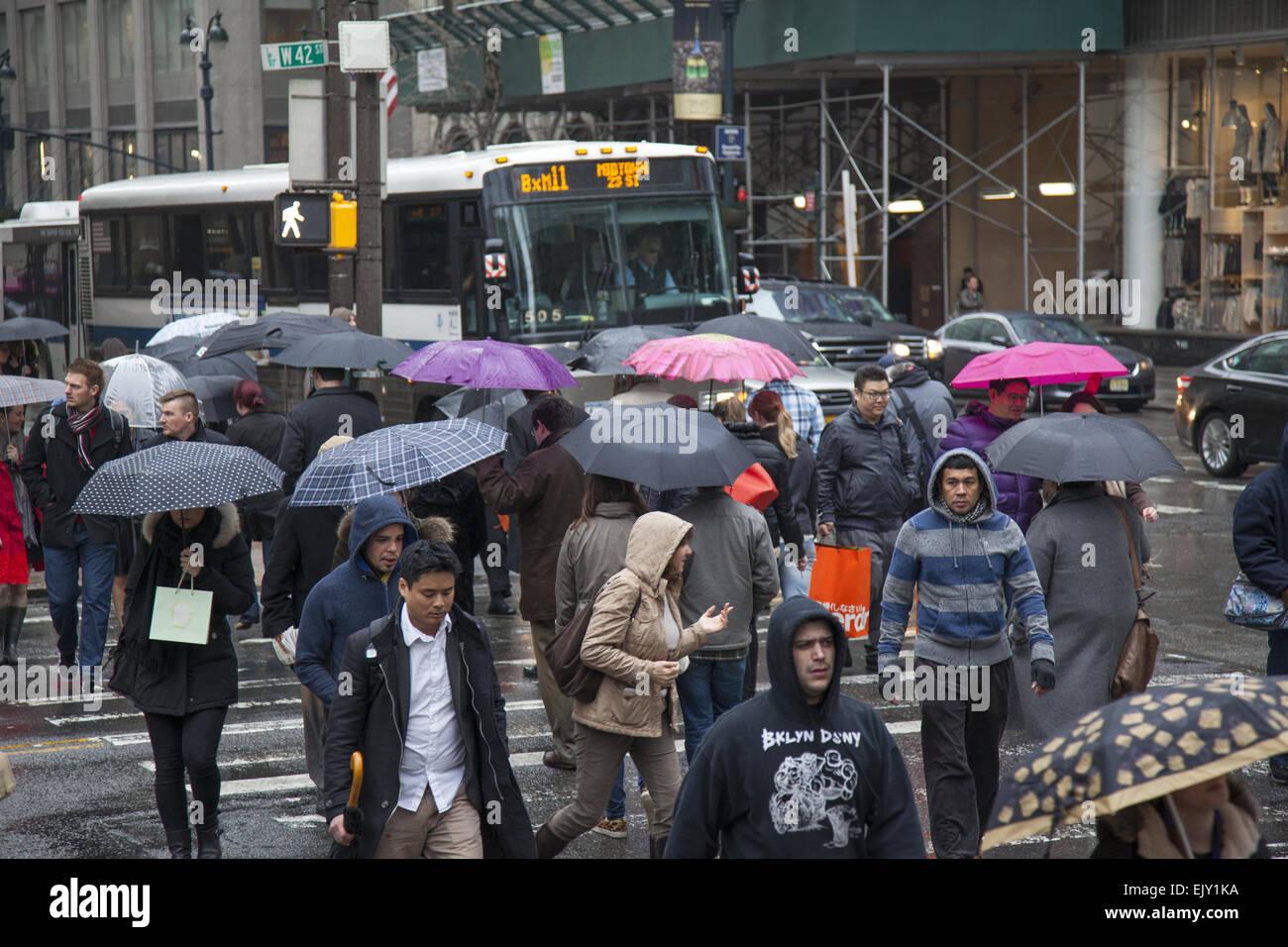 Die Straße bleibt an einem regnerischen Tag in Midtown Manhattan mit Sonnenschirmen, beschäftigt. Stockbild