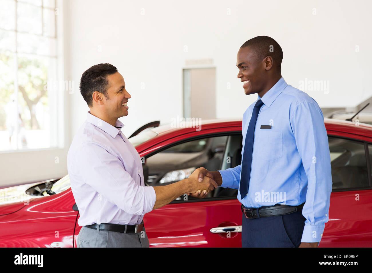 lächelnde afrikanische amerikanische Auto Händler Handshake mit Kunden Stockbild