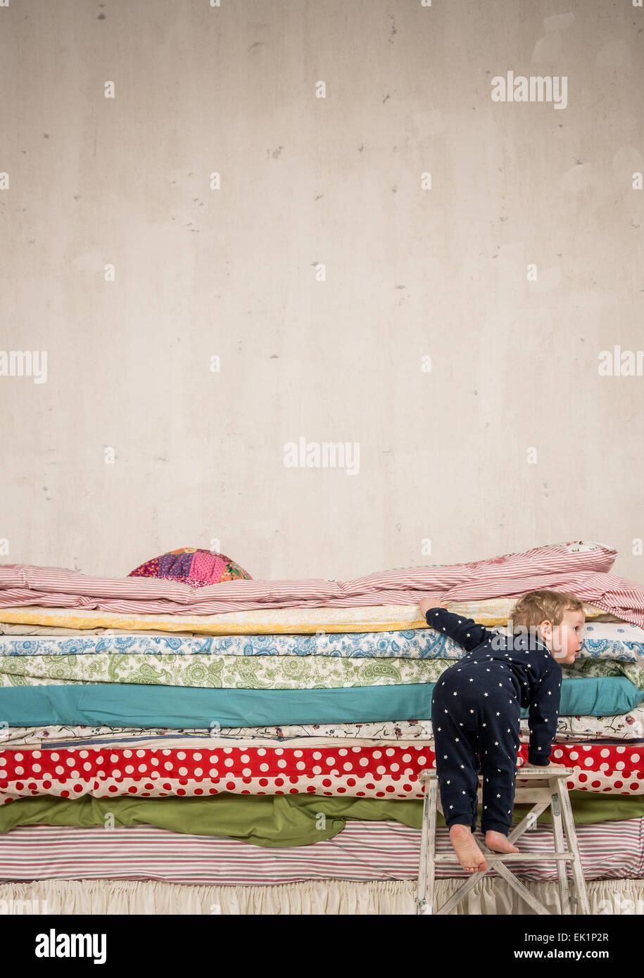 Prinzessin auf der erbse bett  Kind klettert auf dem Bett mit vielen Quilts - Prinzessin und die ...