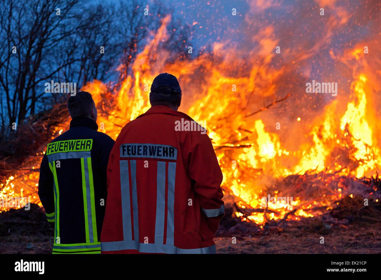 Feuerwehrleute beobachten Osterfeuer, Neetze, Niedersachsen, Deutschland Stockbild