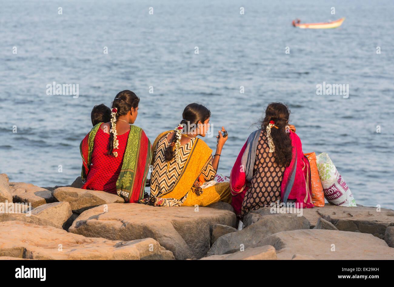 Bunt gekleidete Mädchen, gesellig Familie sitzen im Chat auf den felsigen Strand Küste bei Pondicherry oder Puducherry, Stockfoto