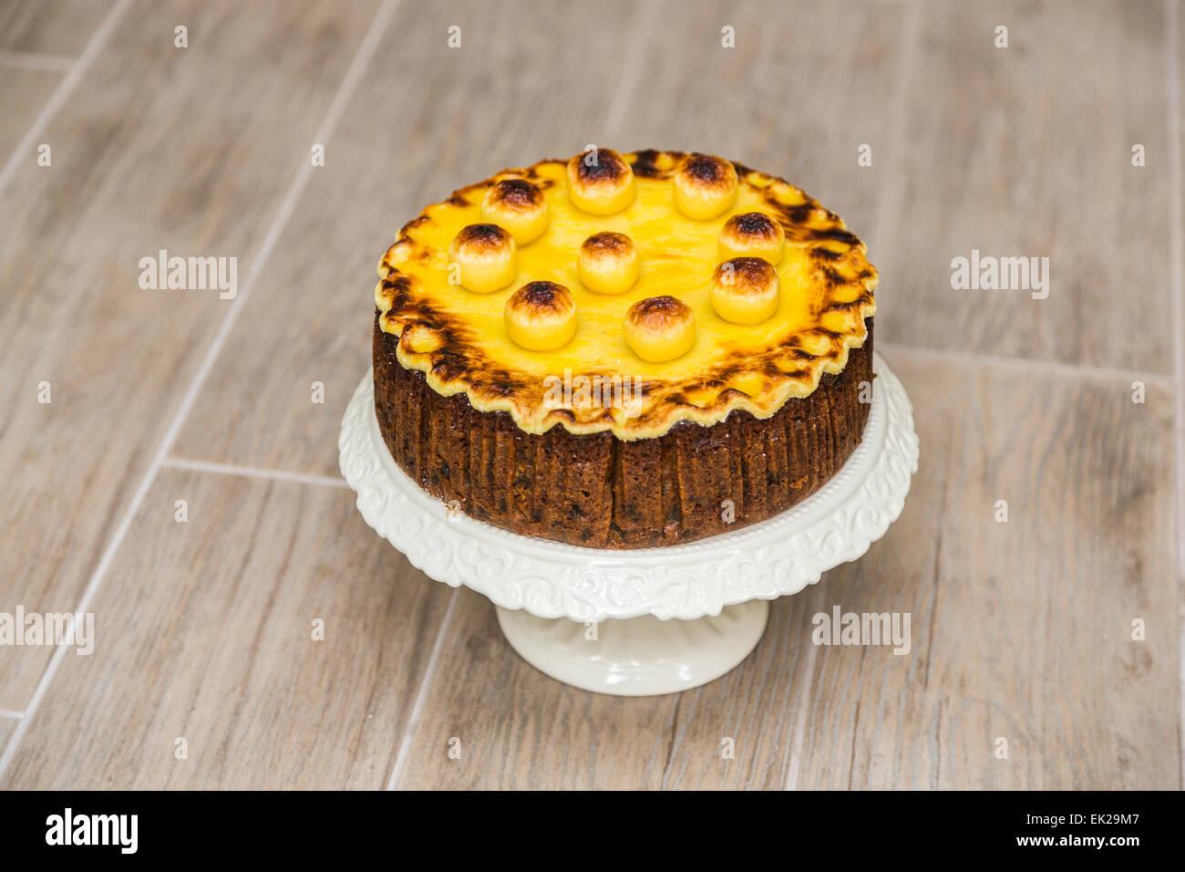 Traditionelles hausgemachtes Simnel Kuchen auf eine Kuchenplatte Weißware für Ostern - Obstkuchen mit Stockbild