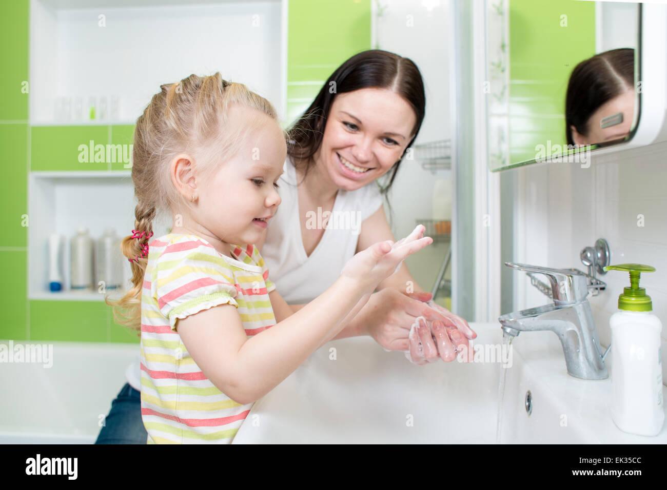 Glückliche Mutter und Kind Händewaschen mit Seife im Badezimmer ...