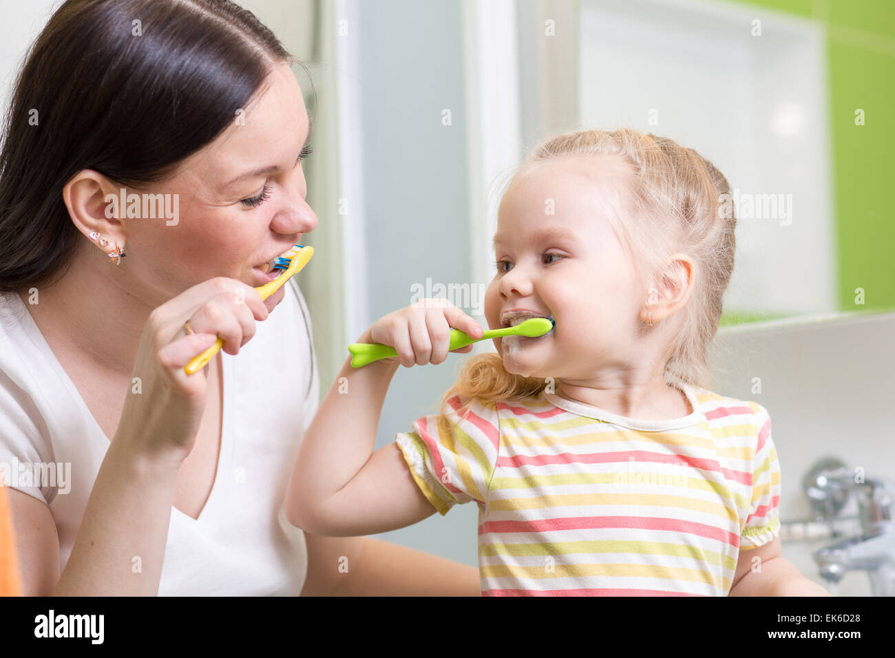 süße Mutter lehrt Kinder Zähne putzen Stockbild
