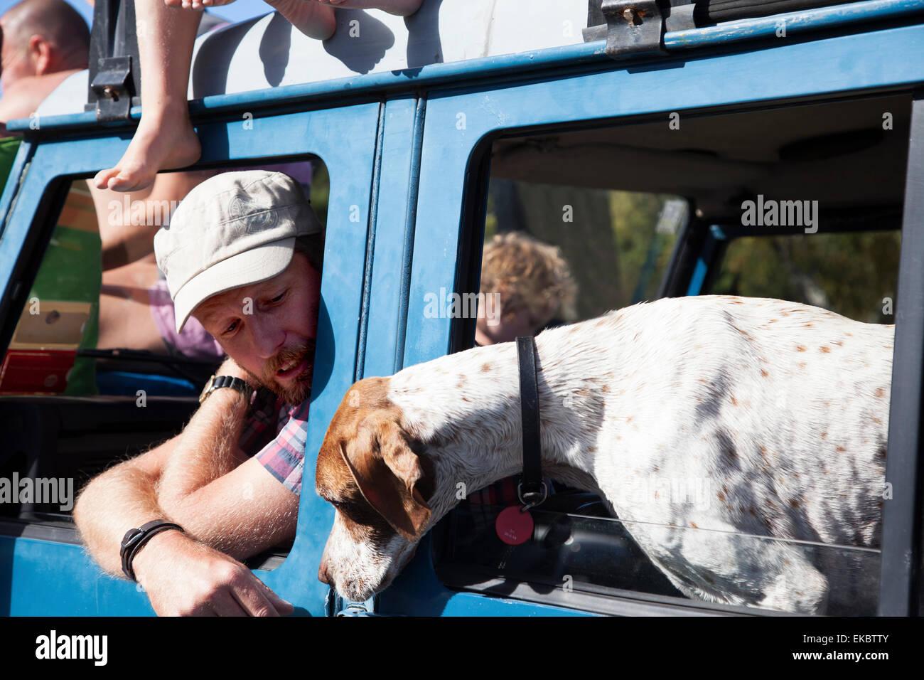 Reifer Mann und Hund gelehnt von off Road Fahrzeugscheiben, Lake Okareka, Neuseeland Stockbild