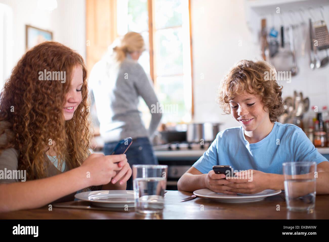 Geschwister mit Smartphone am Esstisch Stockbild