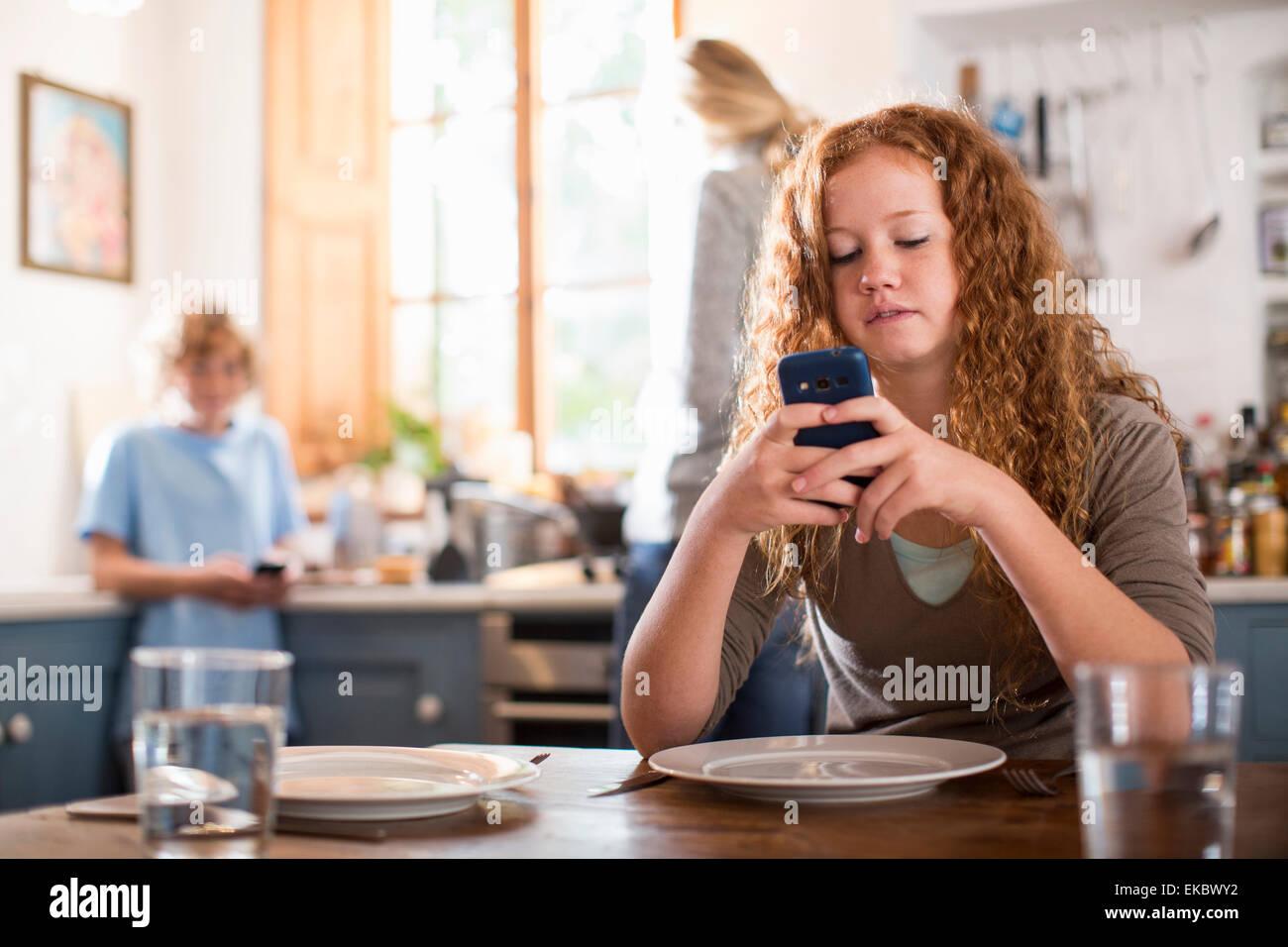 Teenager-Mädchen mit Smartphone am Esstisch Stockbild