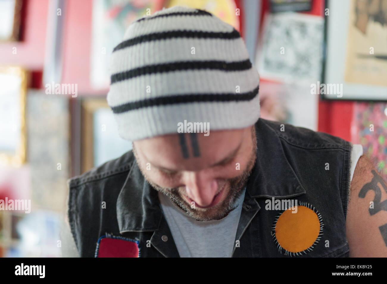 Nahaufnahme eines männlichen Punk-Ladenbesitzer lächelnd und blickte in Vintage Spielzeug-shop Stockbild