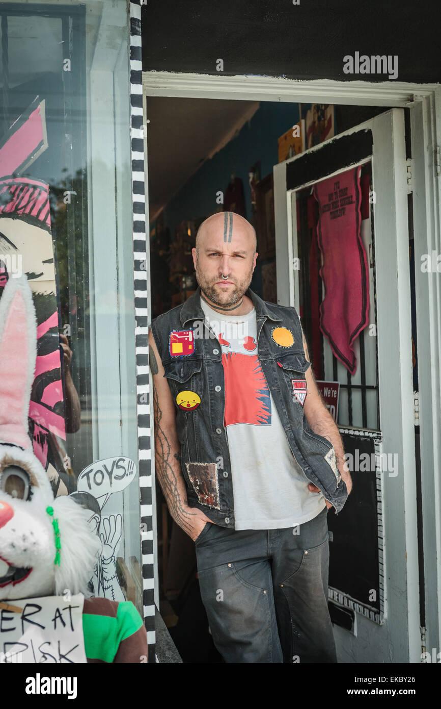 Porträt von männlichen Punk-Ladenbesitzer Vintage Spielzeug Shop Tür gelehnt Stockbild