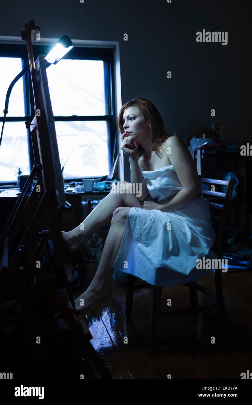 Mitte Erwachsene Frau sitzt vor der Staffelei, starrte auf Leinwand Stockbild