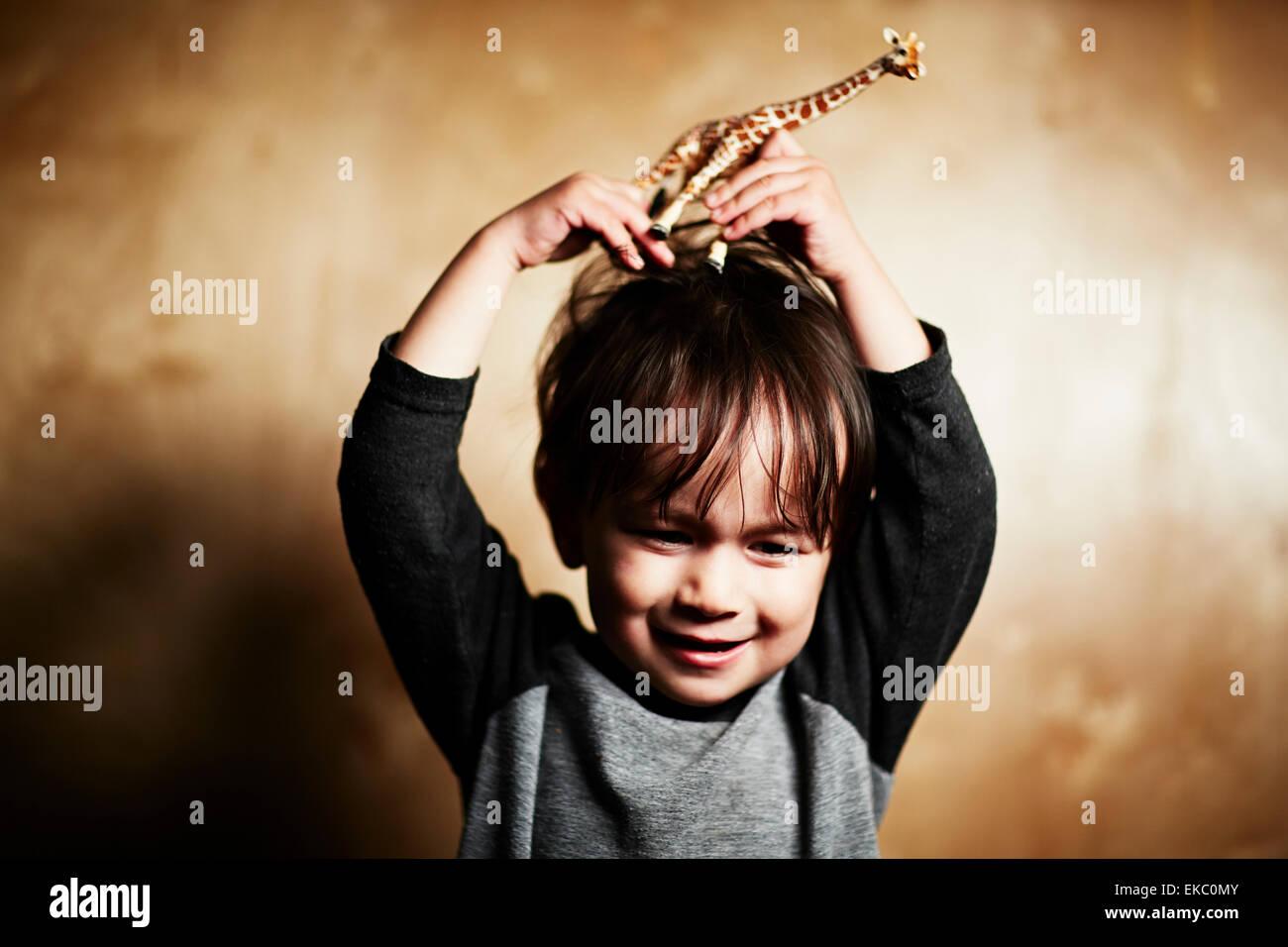 Porträt von niedlichen männliche Kleinkind Spielzeug Giraffe am Kopf halten Stockbild