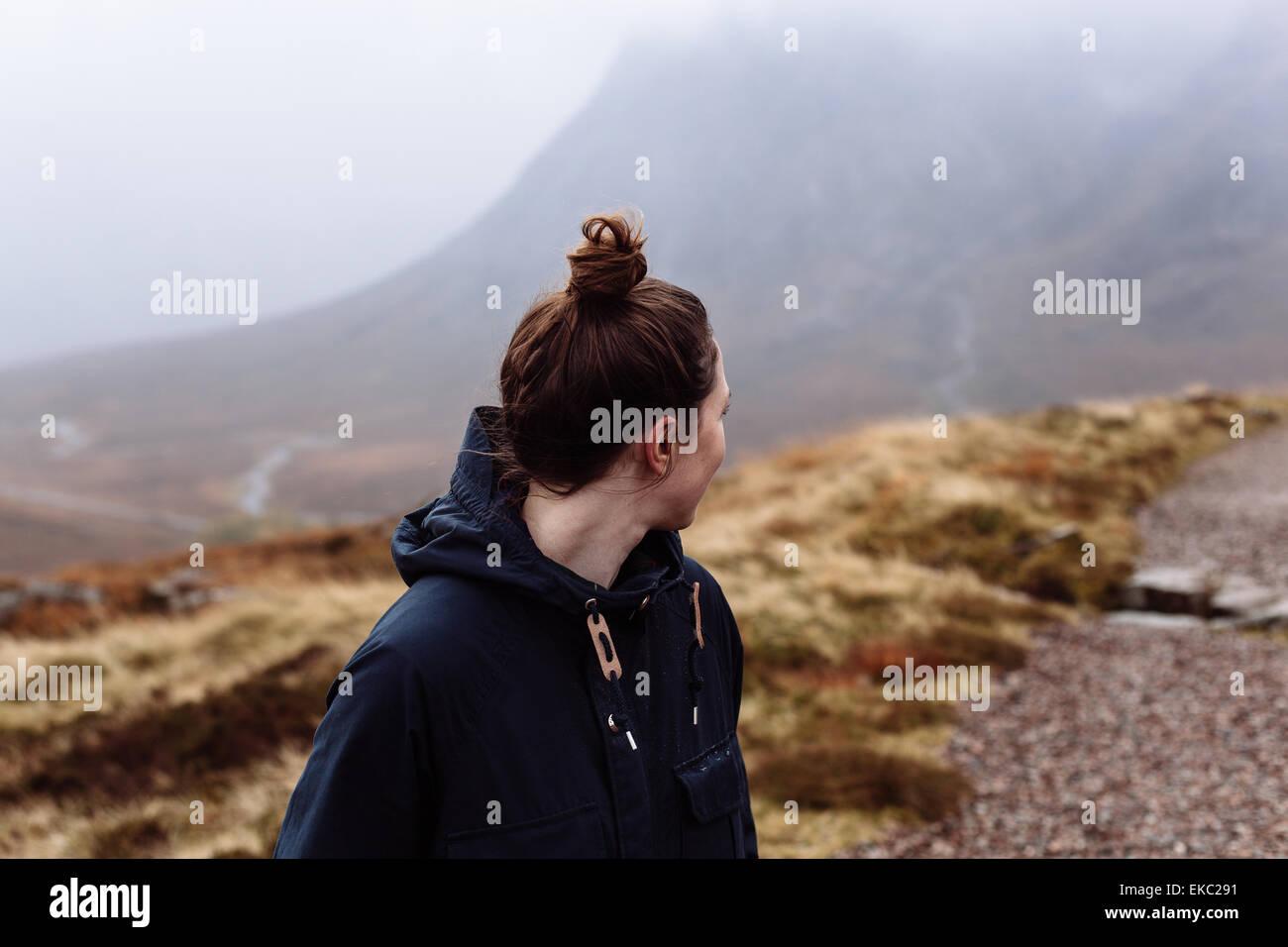 Frau auf der Suche über die Schulter in Richtung Berge Stockbild
