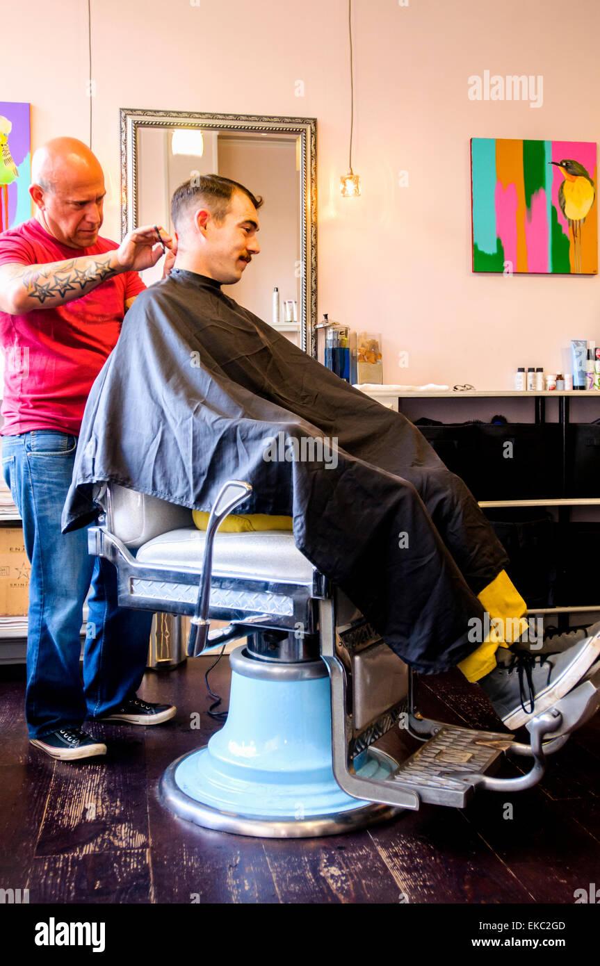 Junger Mann mit seiner Haare schneiden Stockbild