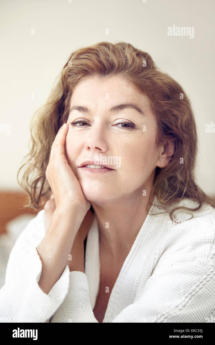 Porträt von Reife Frau ruht Hand auf Gesicht Stockbild