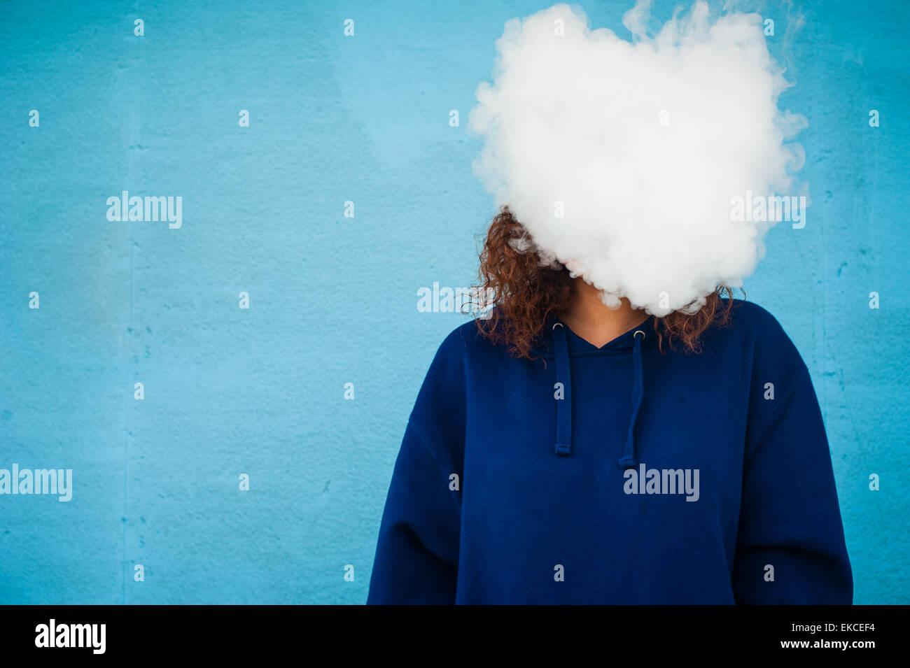 Junge Frau mit dem Kopf in einer Wolke aus Dampf Rauch Stockbild