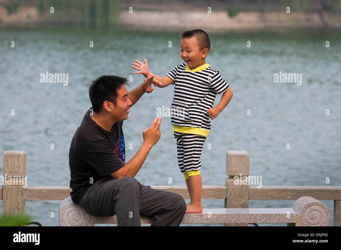 Vater und Sohn ausleben Schwertkampf sah sie bei der Kaiserin Schlosspark, Kaifeng, Henan Provinz, China Stockbild
